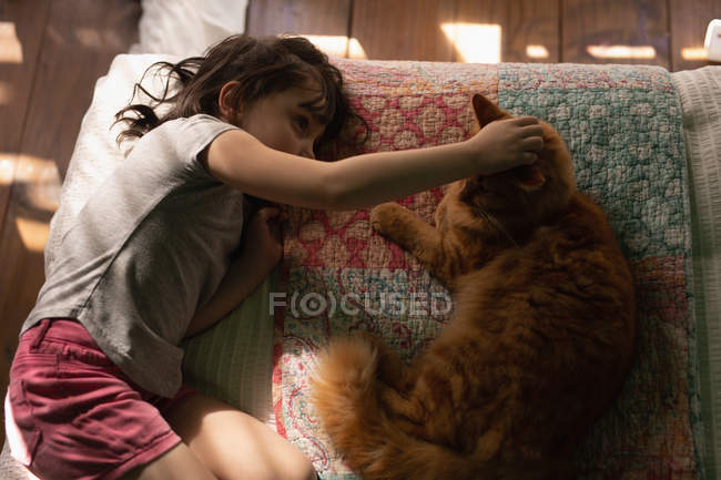 Невинная девушка играет с котом дома — стоковое фото