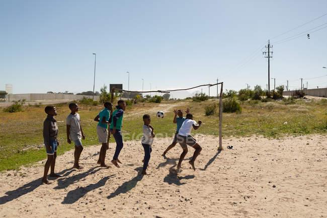 Enfants jouant au football dans le sol par une journée ensoleillée — Photo de stock