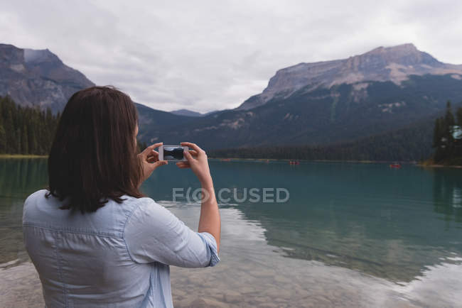 Rear view of woman clicking photos with mobile phone near lakeside — Stock Photo