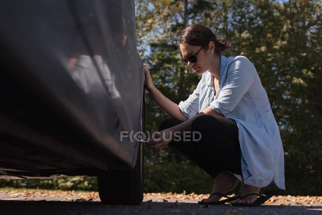 Mulher bonita verificando um pneu em uma estrada — Fotografia de Stock