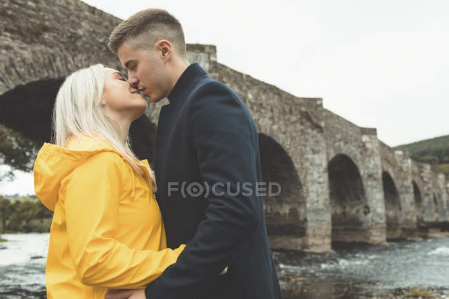 Romántica pareja besándose cerca de río - foto de stock