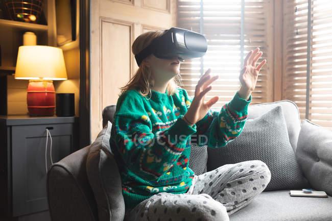 Жінка за допомогою віртуальної реальності гарнітуру на дивані у вітальні на дому — стокове фото