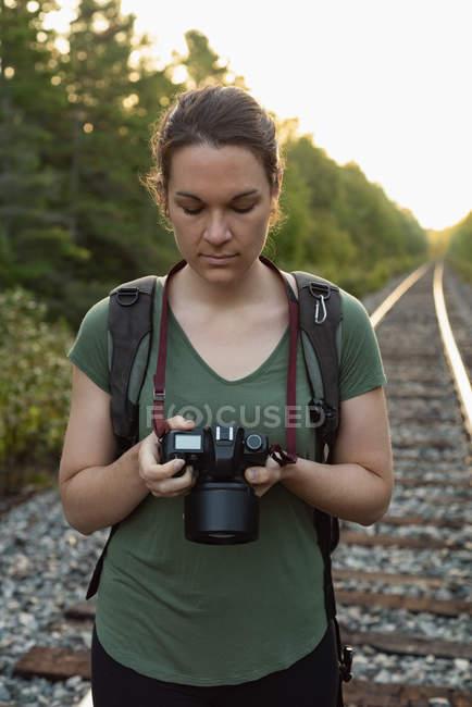 Женщина просматривает фотографии на цифровой фотоаппарат — стоковое фото