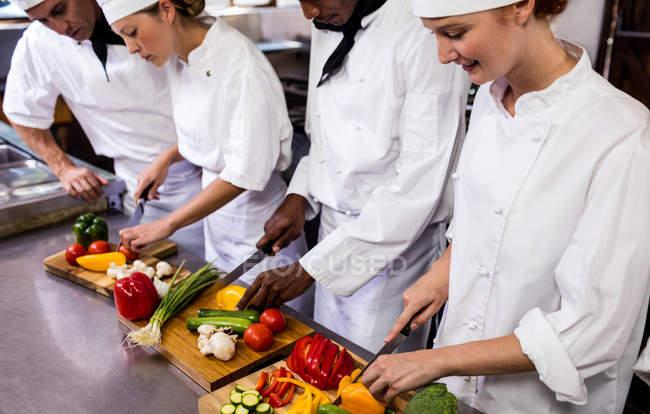 Gruppe von Chef Hacken Gemüse in der Küche — Stockfoto