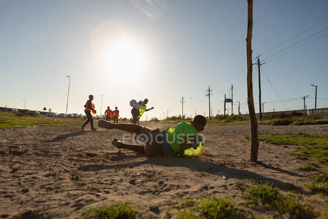 Niños jugando al fútbol en el suelo en un día soleado - foto de stock