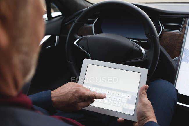 Metà sezione di uomo d'affari utilizzando tablet digitale in una macchina — Foto stock