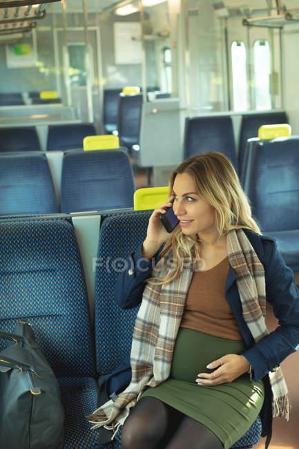 Hermosa mujer embarazada hablando por teléfono móvil mientras viaja en tren - foto de stock
