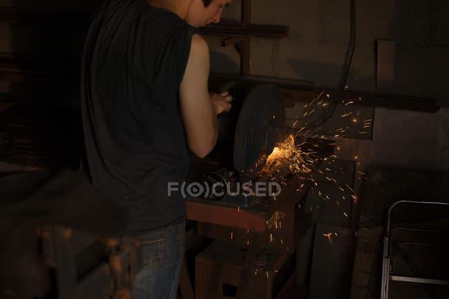 Metalsmith femelle à l'aide de machine de coupe métallique en usine — Photo de stock