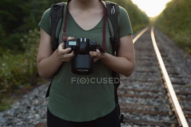 Seção intermediária da mulher revisando fotos na câmera digital — Fotografia de Stock