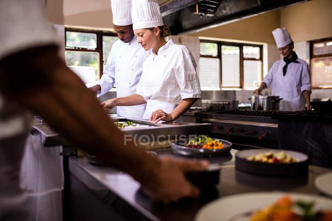 Chefs trabajando en cocina en restaurante - foto de stock