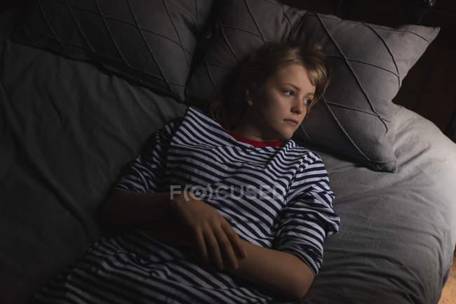 Mujer reflexiva relajarse en la cama en el dormitorio — Stock Photo
