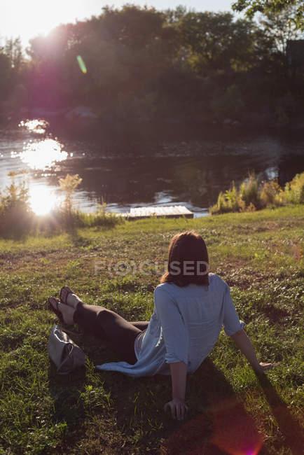 Vista posteriore della donna rilassante vicino al lungofiume — Foto stock