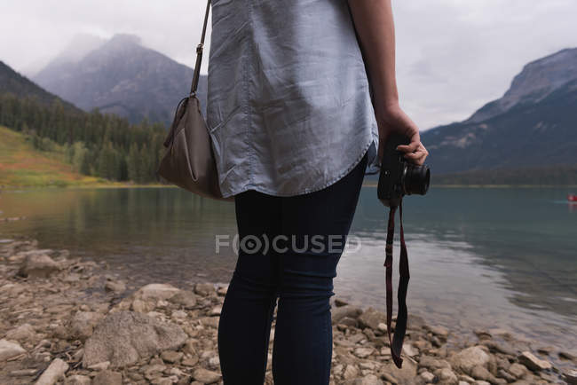 Mid section of woman stranding with camera near lakeside — Stock Photo