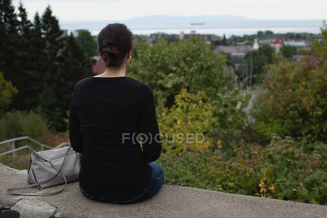 Visão traseira da mulher sentada na parede circundante — Fotografia de Stock