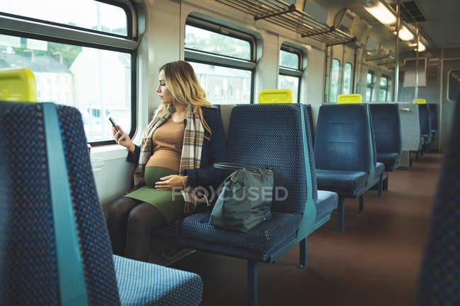 Красива вагітна жінка використання мобільного телефону під час вашого перебування в поїзді — стокове фото