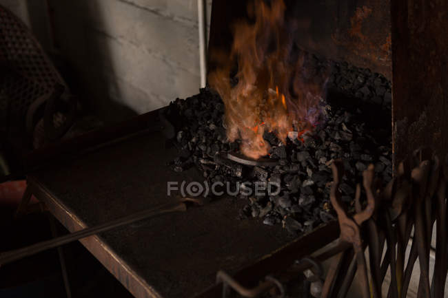 Horseshoe being heated in fire at factory — Stock Photo