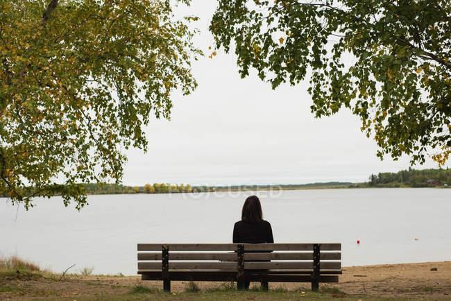 Вид сзади женщины, сидящей на скамейке у реки — стоковое фото