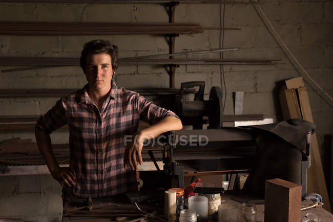 Portrait of female metalsmith standing in factory — Stock Photo