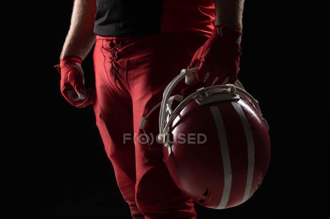Средняя секция американского футболиста, стоящего в шлеме на черном фоне — стоковое фото