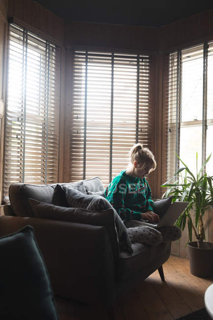 Woman using laptop in living room at home — Stock Photo