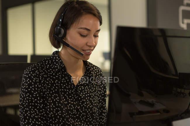 Ejecutivo de servicio al cliente hablando de auricular en el escritorio en la oficina - foto de stock