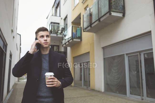 Mann benutzt Handy beim Kaffeetrinken — Stockfoto