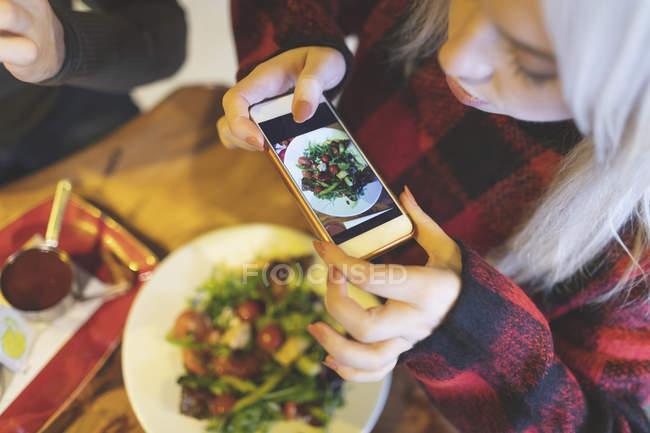 Frais généraux de photo prise femme de nourriture au café — Photo de stock