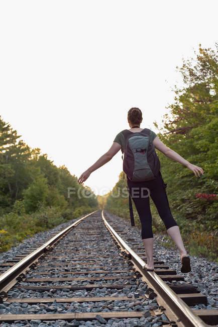 Visão traseira da mulher andando em uma trilha ferroviária — Fotografia de Stock
