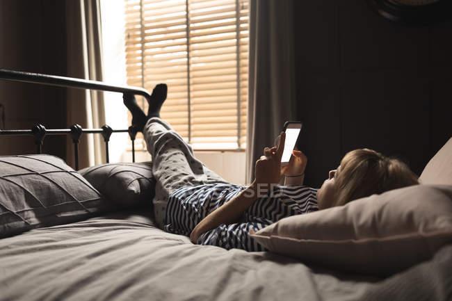 Женщина с мобильного телефона на кровати в спальне на дому — стоковое фото