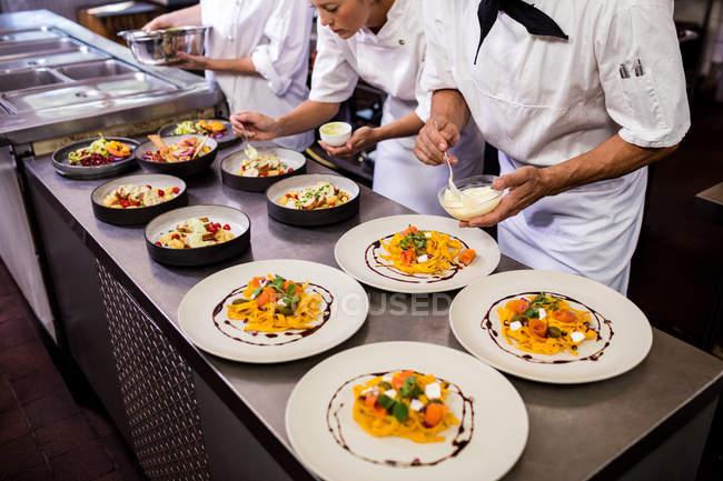 Koch, Garnieren von Speisen auf Platten in Küche — Stockfoto