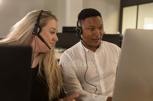 Customer service executives talking on headset at desk in office — Stock Photo