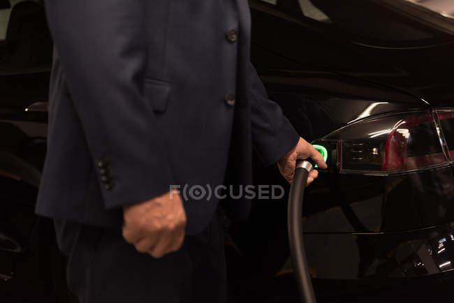 Section médiane de l'homme d'affaires, voiture électrique à la station de recharge de charge — Photo de stock