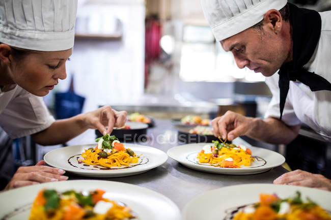 Chef garnishing food on plates in kitchen — Stock Photo