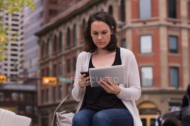 Donna che utilizza il telefono cellulare e tablet digitale in città — Foto stock
