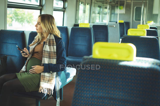 Pregnant woman looking through window while using mobile phone in train — Stock Photo