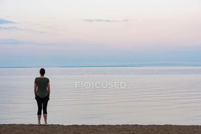Вид сзади на женщину, стоящую на пляже — стоковое фото
