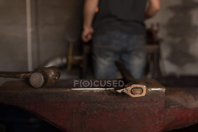 Закри інструменти тримається на ковадлі заводі — стокове фото