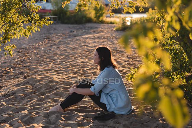 Mulher relaxante perto da ribeira em um dia ensolarado — Fotografia de Stock