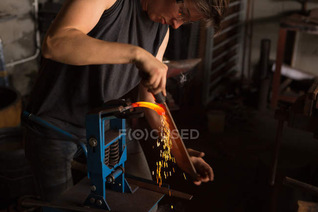 Attentive female metalsmith shaping horseshoe in factory — Stock Photo