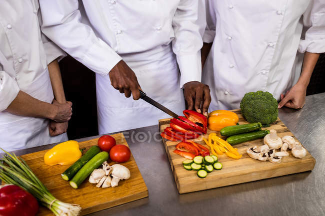 Mid section of chef chopping vegetable in kitchen — Stock Photo