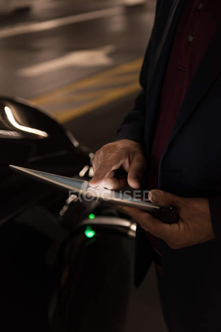 Mid section of businessman using digital tablet while charging electric car — Stock Photo