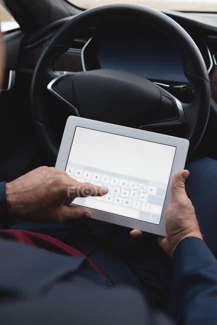 Mid section of businessman using digital tablet in a car — Stock Photo