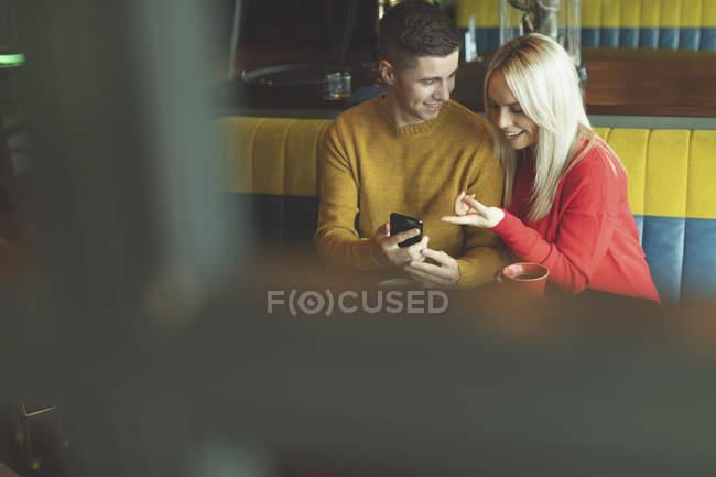 Пара, обсуждая на мобильном телефоне в кафе — стоковое фото