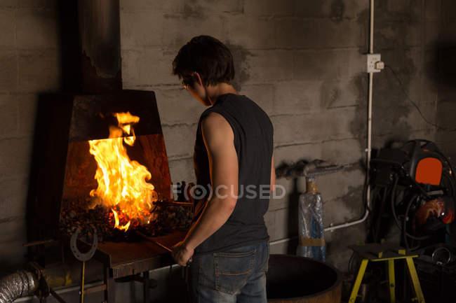 Femme forgeron chauffage fer à cheval dans le feu à l'usine — Photo de stock