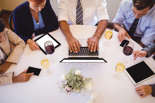 Vista de alto ángulo de la gente de negocios utilizando dispositivos multimedia en el restaurante - foto de stock