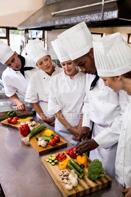 Jefe de cocina enseñando a su equipo a cortar verduras en la cocina - foto de stock