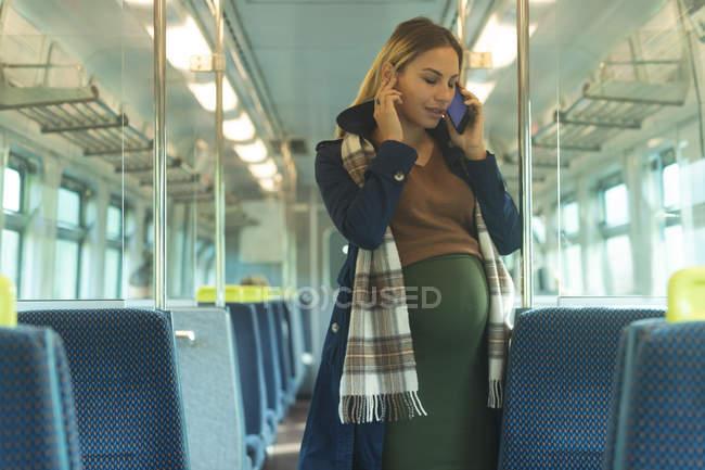 Mujer embarazada hablando en el móvil mientras viaja en tren - foto de stock