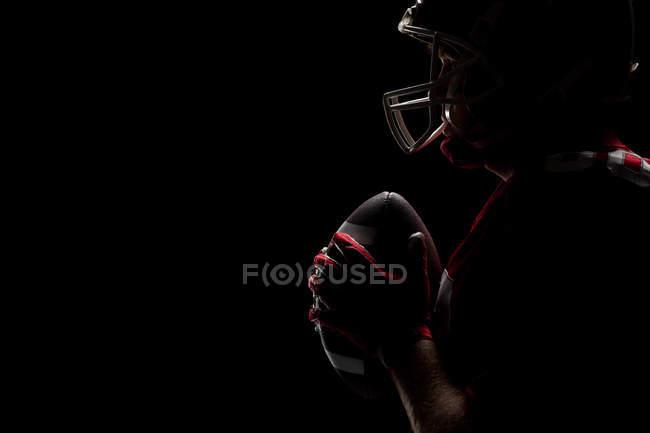 Вид сбоку на американского футболиста, стоящего со шлемом и мячом — стоковое фото