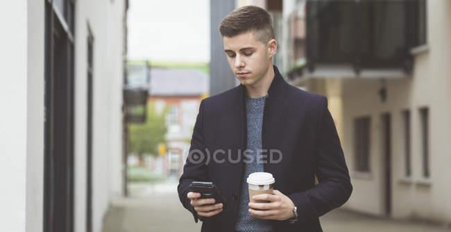 Молодой человек, с помощью мобильного телефона во время кофе — стоковое фото