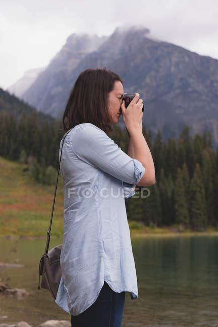 Vista laterale della donna cliccando foto con fotocamera vicino al lago — Foto stock